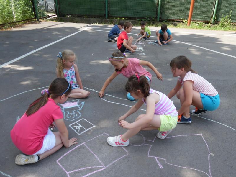 dzieci na boisku rysują kredą