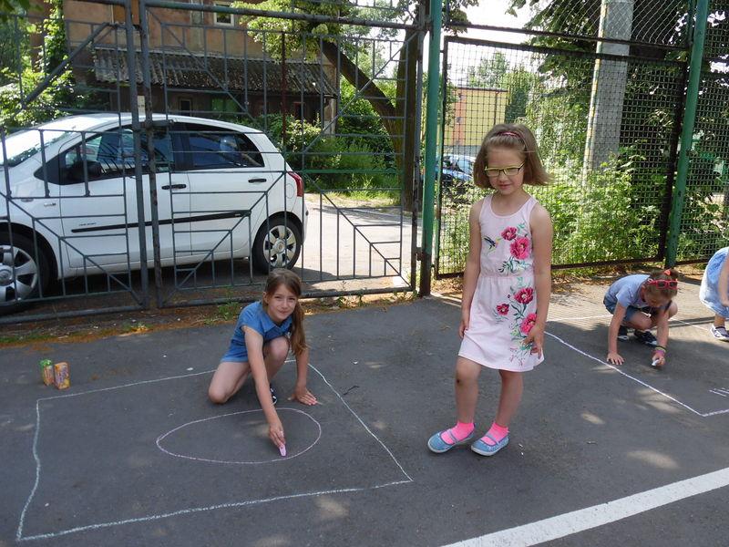 dziewczynki wykonujące prace plastyczną na boisku szkolnym